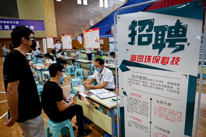 A job seeker talks with a human resource official at a job fair in Zhengzhou, July 2020. Photo: Bloomberg