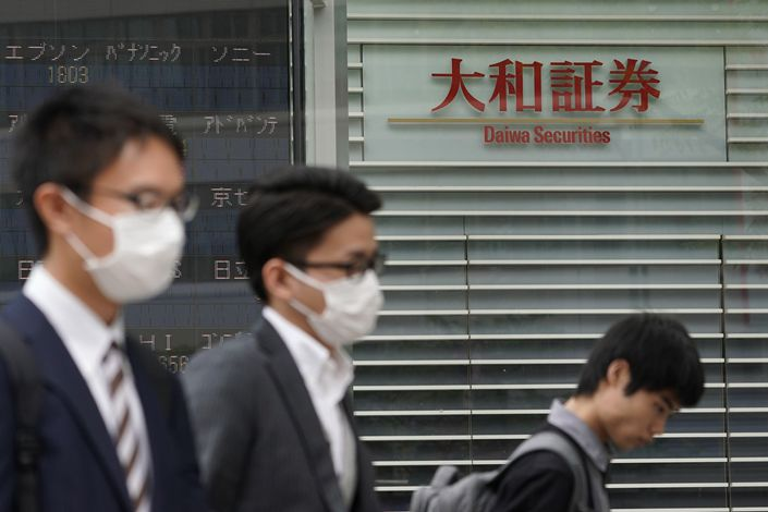 Pedestrians walk past the headquarters of Daiwa Securities in Tokyo on April 23.