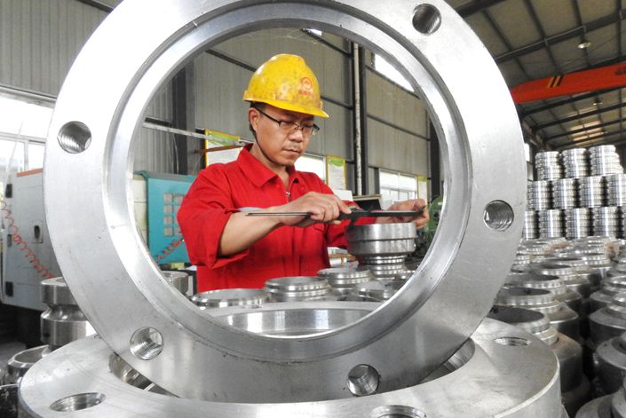 A worker processes parts for a batch of fluid handling equipment on July 20 at a company in Lianyungang, East China's Jiangsu province.