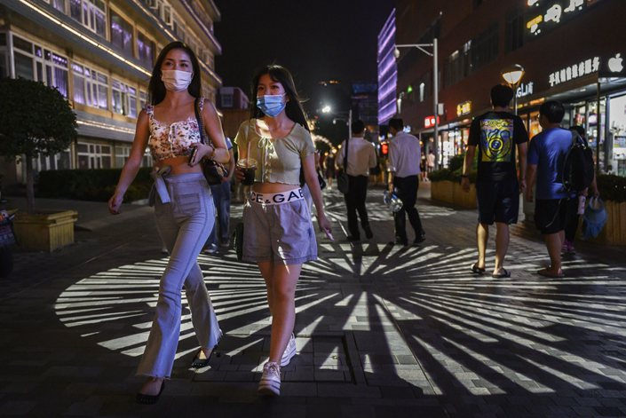 People wear protective masks in Beijing's Sanlitun shopping and nightlife area on Aug. 14.