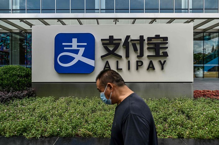 A pedestrian walks past a sign for Alipay outside of Ant Group's offices in Shanghai on Friday.