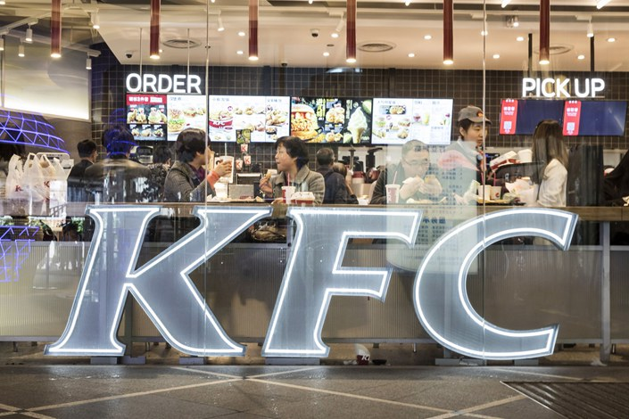 Signage for KFC is displayed in the window of a restaurant in Shanghai on March 19, 2019. Photog: Bloomberg