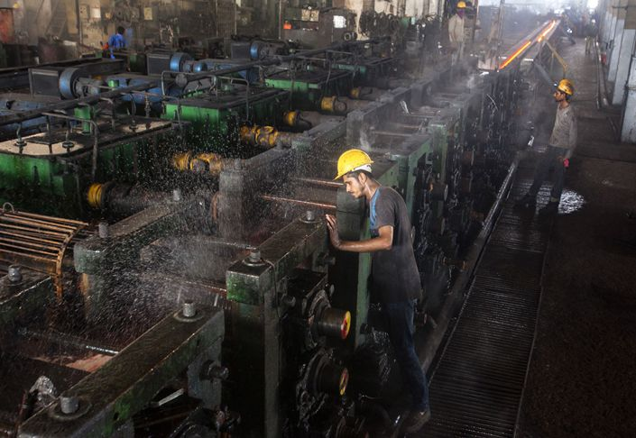Employees supervise production in the rolling mill area inside an Agha Steel Industries Ltd. plant in Karachi, Pakistan, on June 3, 2017.  Photo: Bloomberg