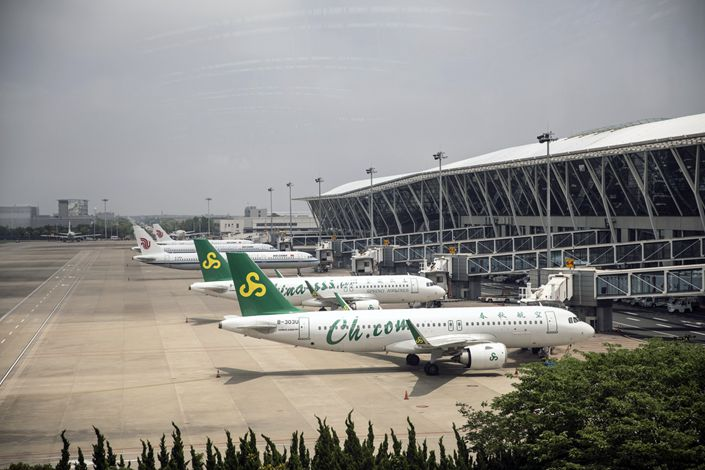 Spring Airlines Co. and Cathay Pacific Airways Ltd.'s Cathay Dragon aircraft stand on the tarmac at the Pudong International Airport in Shanghai on June 8. Photo: Bloomberg