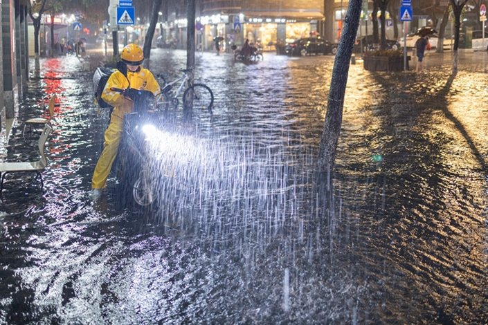 A Meituan driver makes a delivery during a downpour on May 20 in Guangzhou, South China's Guangdong province.