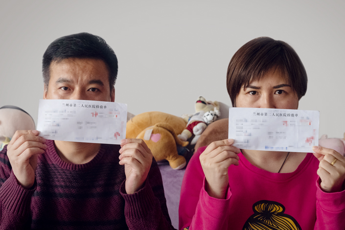 Zhu Zhi and his wife Zhou Xing hold up their laboratory results.The couple and their daughter all tested positive for brucellosis. Photo: Guo Xianzhong/Caixin