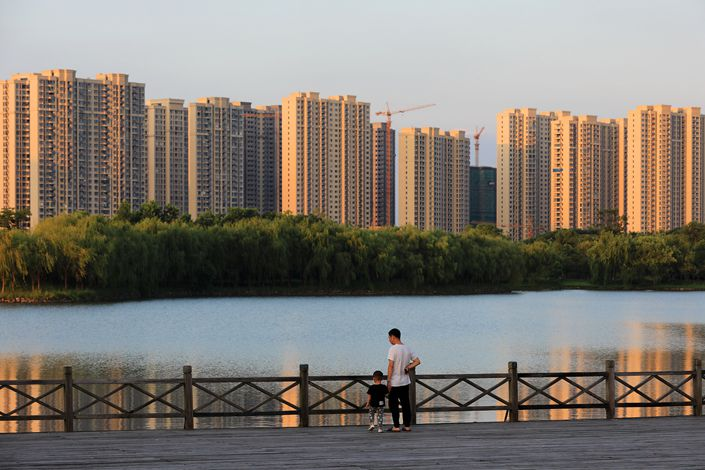 A residential complex under contruction towers over a lake in Huaian, East China's Jiangsu Province, on Aug. 30.