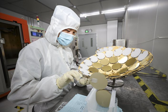 A technician works at a chip company in Huai'an, Jiangsu province, on June 16.