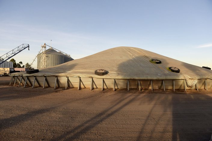 A stock pile of barley sits under a tarpaulin before it is loaded onto trucks and transported to the port for shipping, at Balliang, south of Melbourne, Australia, on May 18. Photo: Bloomberg