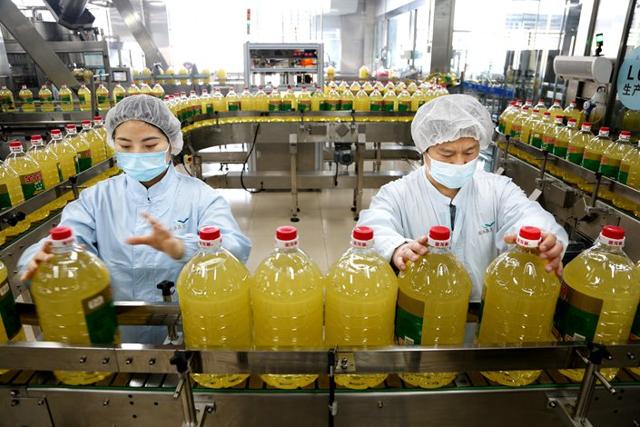 Workers produce cooking oil in an Yihai factory in Lianyungang, East China's Jiangsu province, April 27.