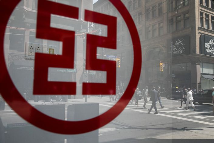 Pedestrians are seen reflected in the window of a Industrial and Commercial Bank of China Ltd. (ICBC) branch in the financial district of Toronto