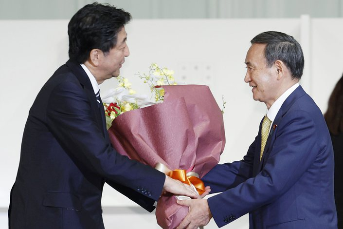 Prime Minister Yoshihide Suga (right) is expected to largely maintain predecessor Shinzo Abe's foreign policy.