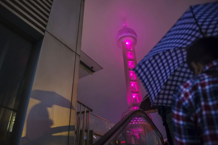 A pedestrian holding an umbrella rides up an escalator as the Oriental Pearl Tower stands illuminated at night in the Lujiazui district of Shanghai