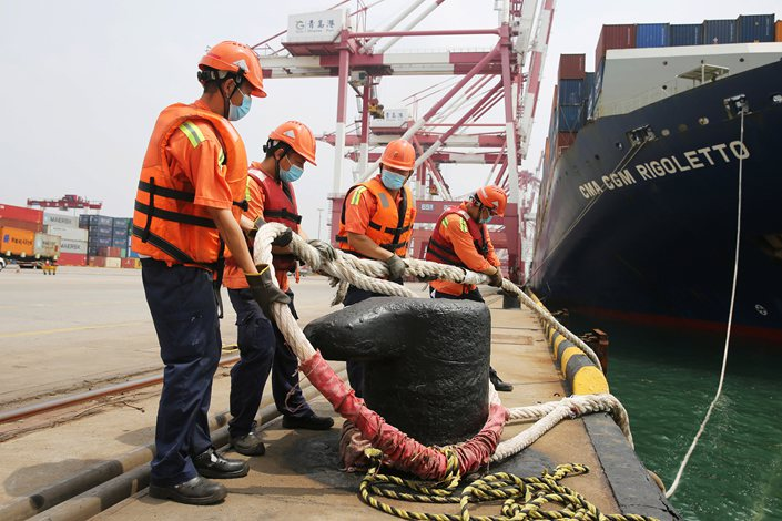 Workers unrope a container ship as it is about to leave port in Qingdao, East China's Shandong province, Sept. 9.