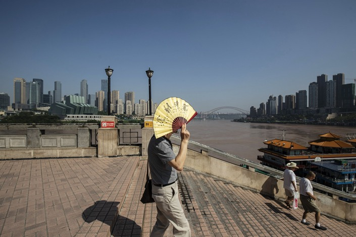 A pedestrian uses a folding fan to shield from the sun as he walks through a square overlooking the Chaotianmen docks in Chongqing on July 28, 2020. Photo: Bloomberg