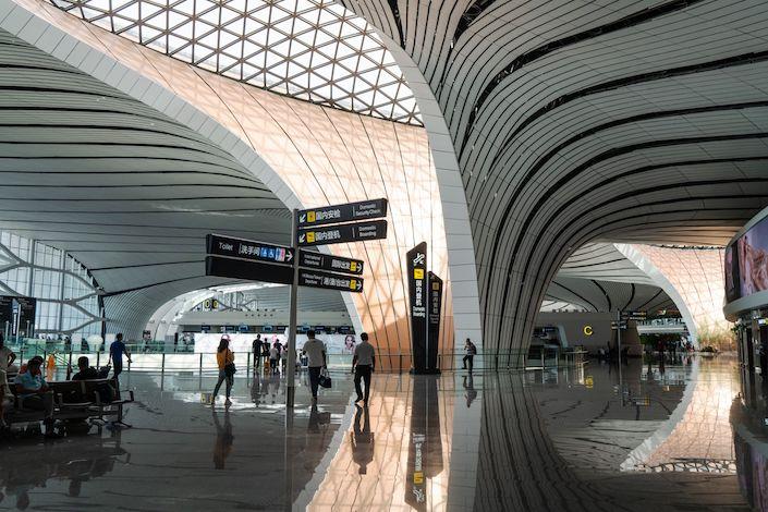Travelers walk through Beijing Daxing International Airport in Beijing