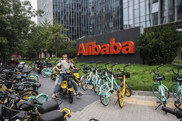 Motorists ride past the Alibaba Group Holding Ltd. logo displayed in front of the company's building in Beijing