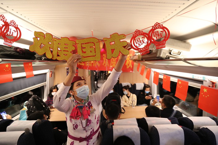 A conductor decorates a train for the National Day holiday during a trip from Chongqing North Railway Station to Wanzhou district in Southwest China's Chongqing municipality on Sept. 30.
