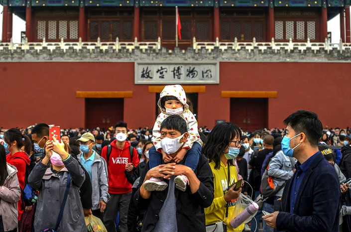 A group of Chinese tourists walk outside the Forbidden City in Beijing on Tuesday.