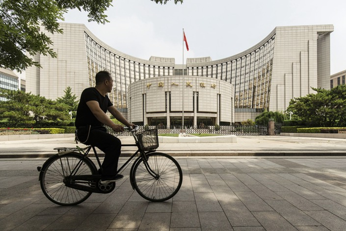 A man rides a bicycle past the People's Bank of China headquarters in Beijing in June 2019.