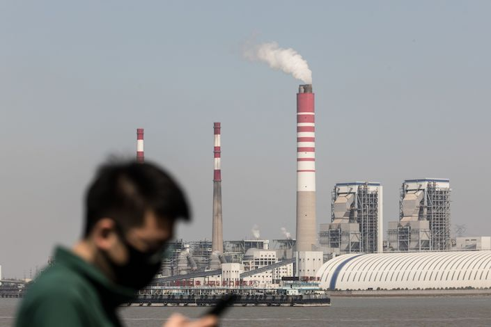 A pedestrian wearing a protective mask uses his mobile phone as a thermal power plant stands across the river in Changshu