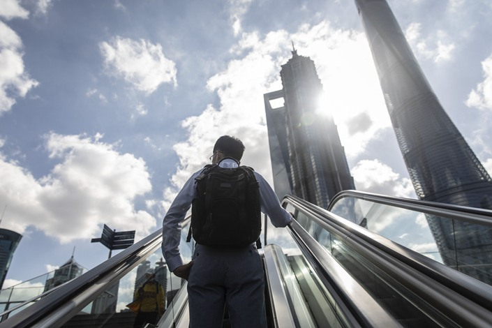 A morning commuter rides an escalator in the Lujiazui Financial District in Shanghai