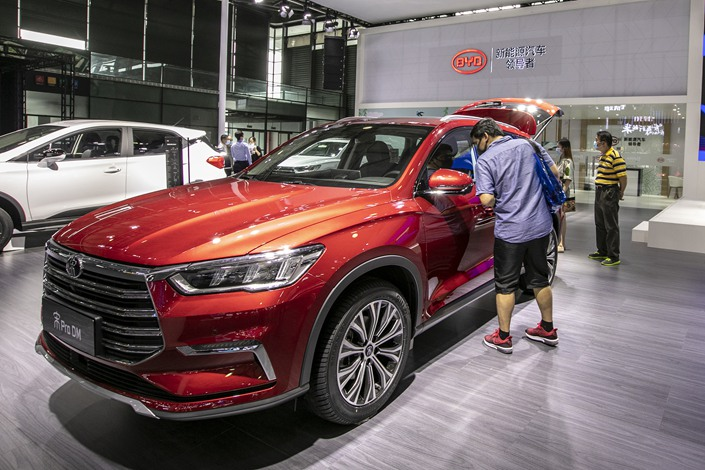 A conference-goer checks out a BYD model at an auto show in Shanghai on Oct 3.