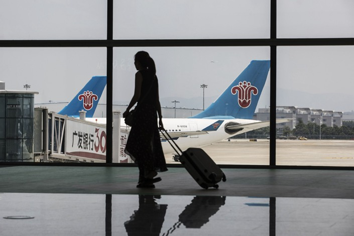 A woman carrying luggage is silhouetted as she walks past aircraft operated by China Southern Airlines Co. sitting on the tarmac at Terminal 2 of the Guangzhou Baiyun International Airport in Guangzhou