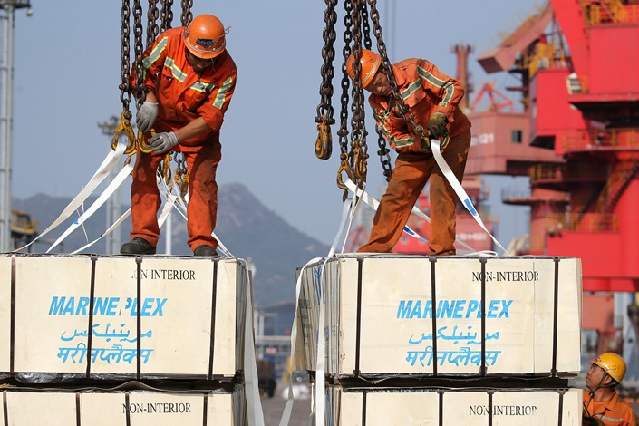 Workers load plywood for export at the port of Lianyungang, East China's Jiangsu province, Oct. 1.
