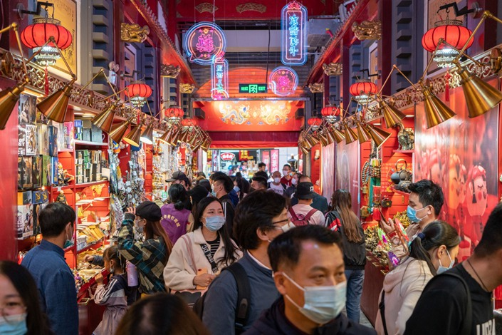Shoppers crowd a path looking at offerings from souvenir shops in Beijing on Oct. 4. Photo: Bloomberg