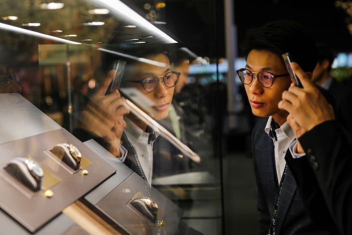A visitor looks at luxury wristwatches on display during day two of the 2019 Baselworld luxury watch and jewellery fair in Basel