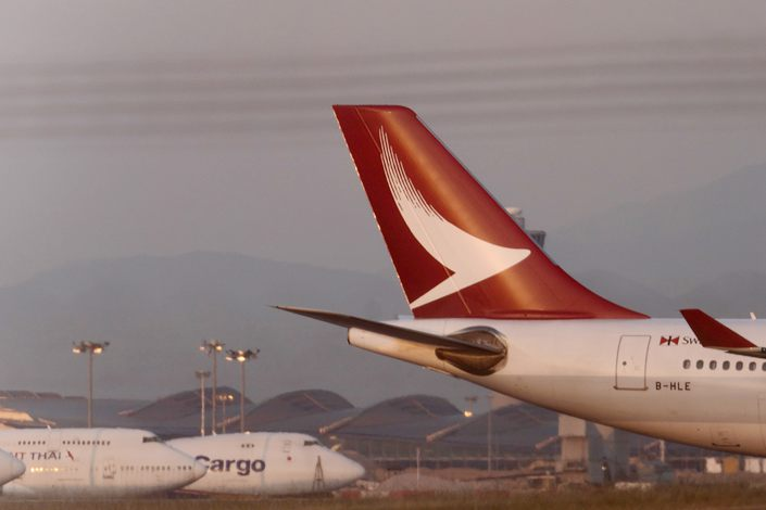 The tail fin of an Airbus SE A330-342 aircraft operated by Cathay Dragon, a unit of Cathay Pacific Airways Ltd., right, is seen at Hong Kong International Airport at dusk in Hong Kong, China, on Saturday, March 11, 2018. Photo: Bloomberg