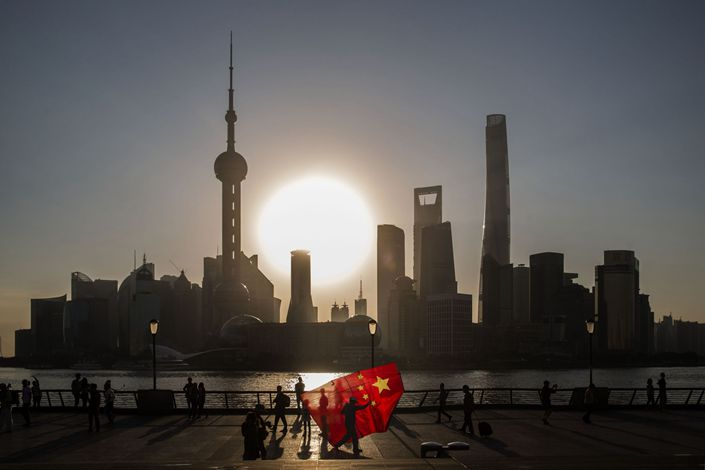 A man carrying a kite in the shape of the Chinese national flag walks along the Bund while buildings of Pudong's Lujiazui financial district stand across the Huangpu River in Shanghai