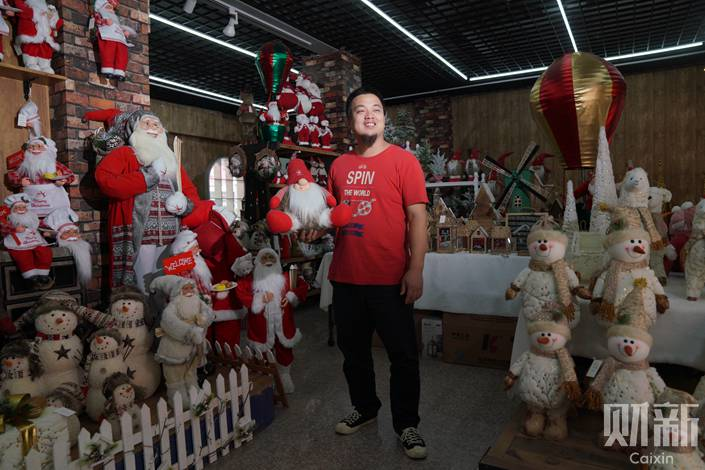 A Christmas goods manufacturer shows a product on Sept. 24 at his store in Yiwu. Photo: Liang Yingfei/Caixin