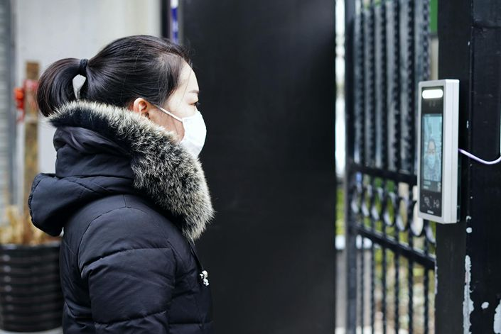 A resident has her face scanned on March 3 before entering a residential compound in Hangzhou, East China's Zhejiang province.