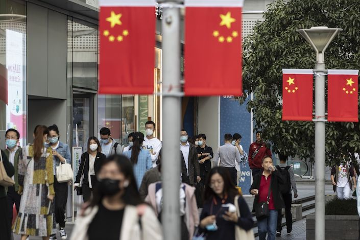 Morning commuters wearing protective masks walk past Chinese flags displayed along Nanjing Road in Shanghai