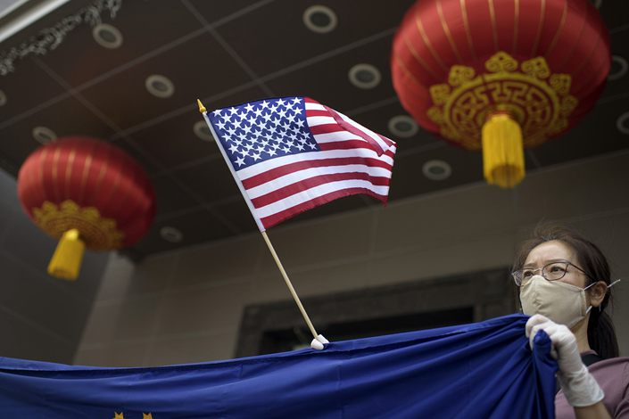 A protester holds a US flag outside of the Chinese consulate in Houston on July 24, after the US State Department ordered China to close the consulate.  Photo: Bloomberg