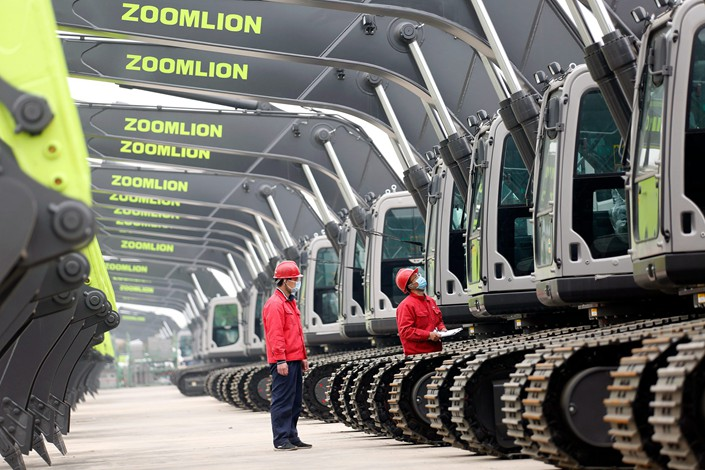 Inspectors examine an excavator before it leaves a Zoomlion factory in Weinan, Northwest China's Shaanxi province, on March 12.