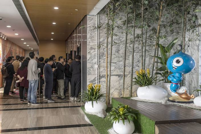 Employees line up for elevators near a company mascot during lunch hour at one of Ant Group Co.'s offices in Hangzhou on Nov. 2. Photo: Bloomberg