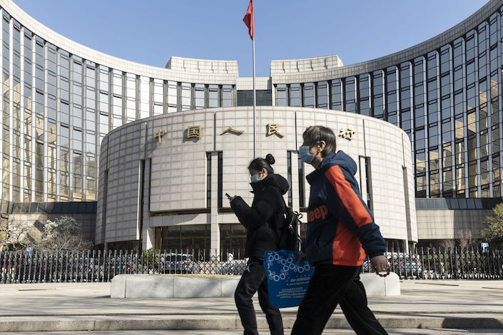 Pedestrians wearing protective masks walk past the People's Bank of China (PBOC) building in Beijing