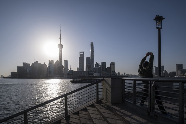 A man stretches on the Bund as skyscrapers of the Pudong Lujiazui Financial District stand across the Huangpu River during sunrise in Shanghai on March 20. Photo: Bloomberg