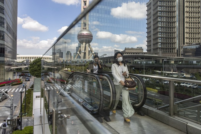 Morning commuters ride an escalator in the Lujiazui Financial District in Shanghai on Oct. 9, 2020.  Photo: Bloomberg