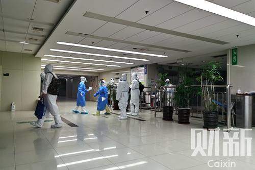 """上海浦东医院""""封院"""",住院部大楼单独隔离,大批防疫人员深夜抵达,进行采样及密接者转运。图/财新记者 包志明"""