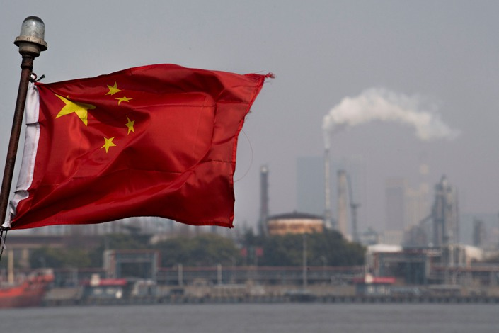 A Chinese flag flutters in front of the Shanghai Gaoqiao Co. Refinery in Shanghai on March 22, 2018. Photo: Bloomberg