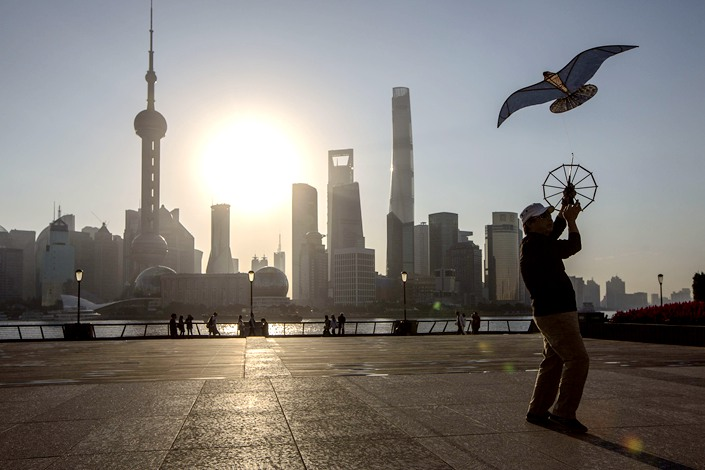 A man flies a kite on the Bund while buildings of Pudong's Lujiazui financial district stand across the Huangpu River as the sun rises in Shanghai