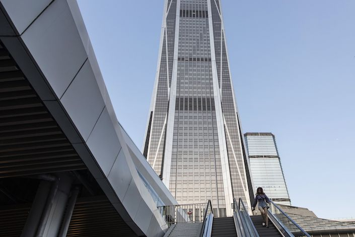 A pedestrian rides an escalator in front of the Ping An Finance Centre in Shenzhen