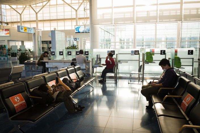 Passengers rest next to social distancing signs displayed on seating at Haneda Airport in Tokyo