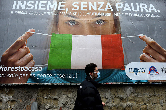 A man walks past a poster that reminds people to wear face masks in Naples, Italy, on March 22.