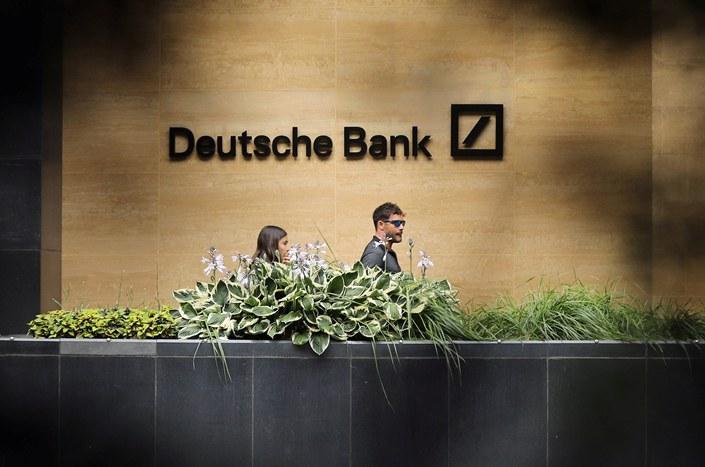 People walk past a Deutsche Bank office in London on July 8.