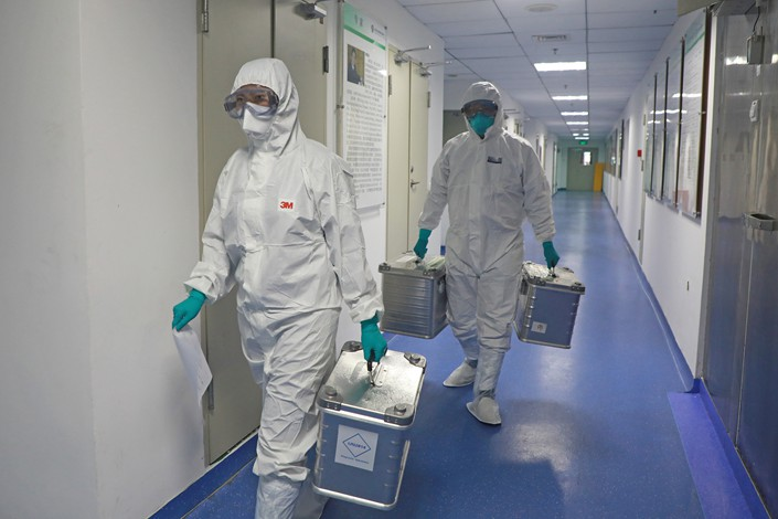Medical workers on March 2 carry samples to a lab at the Shenzhen Center for Disease Control and Prevention in Shenzhen, South China's Guangdong province.